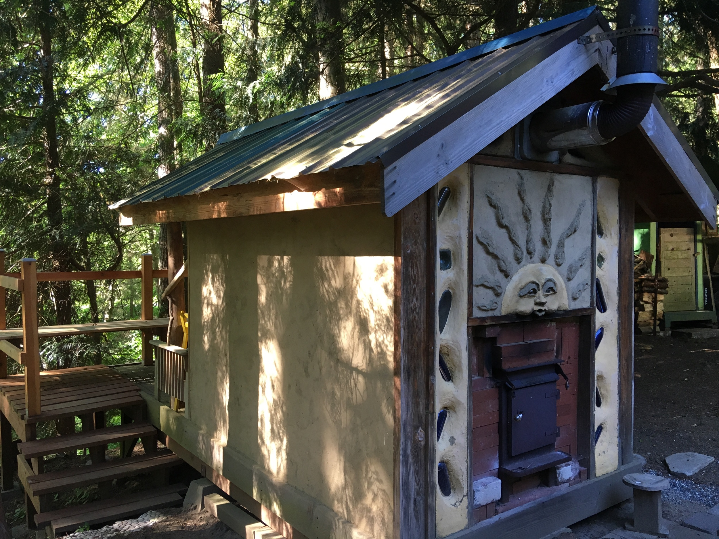 Slip straw sauna with earthen plaster and cob bottle columns.