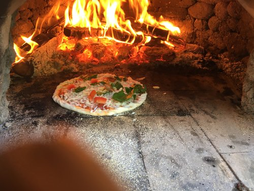 "Clay Oven Cooking Class - It is commonly thought that a baking oven and a pizza oven are one in the same. This is true some of the time-let me explain. A traditional pizza oven typically has the fire in the oven burning while cooking. A baking oven, on the other hand, takes the fire out after it is hot and seals up the door. A pizza oven usually has thinner walls, not as much insulation, thus allowing it to heat up faster. In other words, you could bake out of a pizza oven, but not as long and not as much since it cools down faster without insulation. The pizza oven is primarily for flat breads such as focaccia and ciabatta, and pita and of course meat and vegetable pies such as empanadas. All of this we will explore as we fire up the clay ""pizza""oven and cook a variety of sizzling goodness! You will walk away with tips on how best to fire the oven and get the most out of the heat it produces. We will share with you a few of our favorite recipes, including our popular gluten free dough. Come with an appetite, a pizza topping and a beverage of your choice and be ready for a fantastic culinary experience!cost:$100."