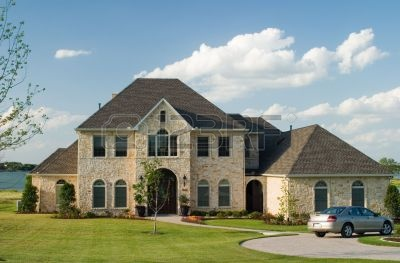 443486-very-large-and-beautiful-stone-and-brick-house-on-a-small-lake-with-generic-car-in-front-circle-driv.jpg