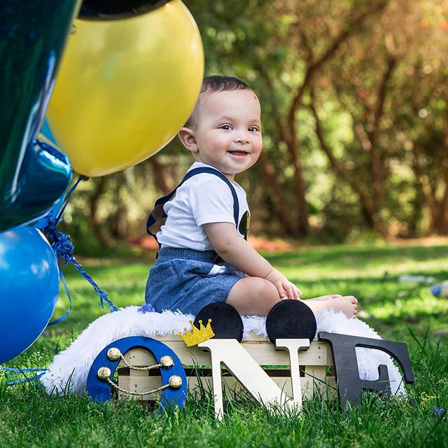 What a cute little guy!   #baby #blue #mickey #balloons #photo #potrait #one #oneyearsold #smile #day #green #sunny #summer #photography #grass #trees