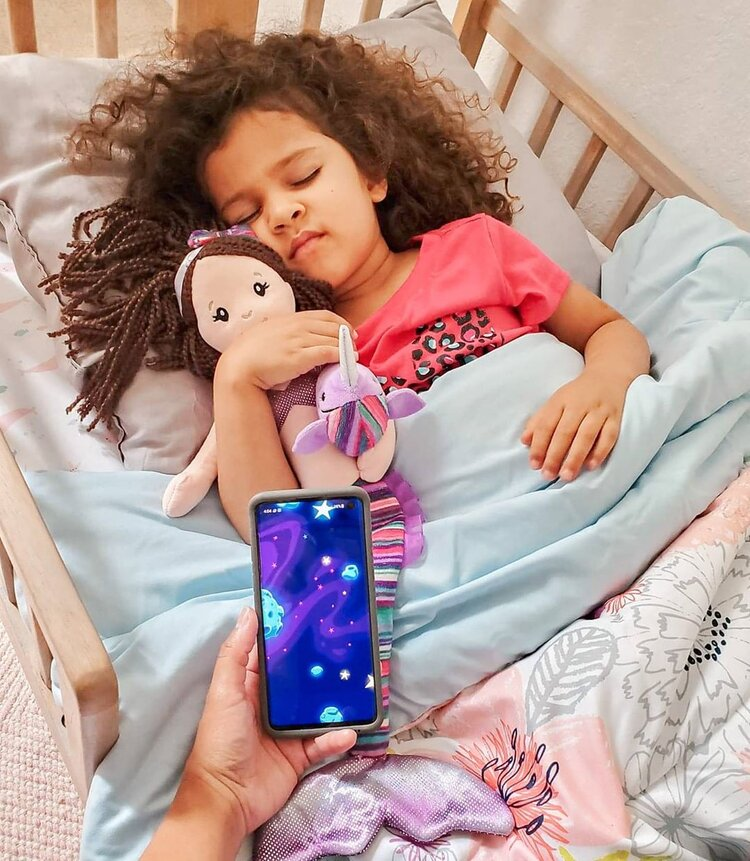 young girl sleeping in crib with moshi app on phone playing above