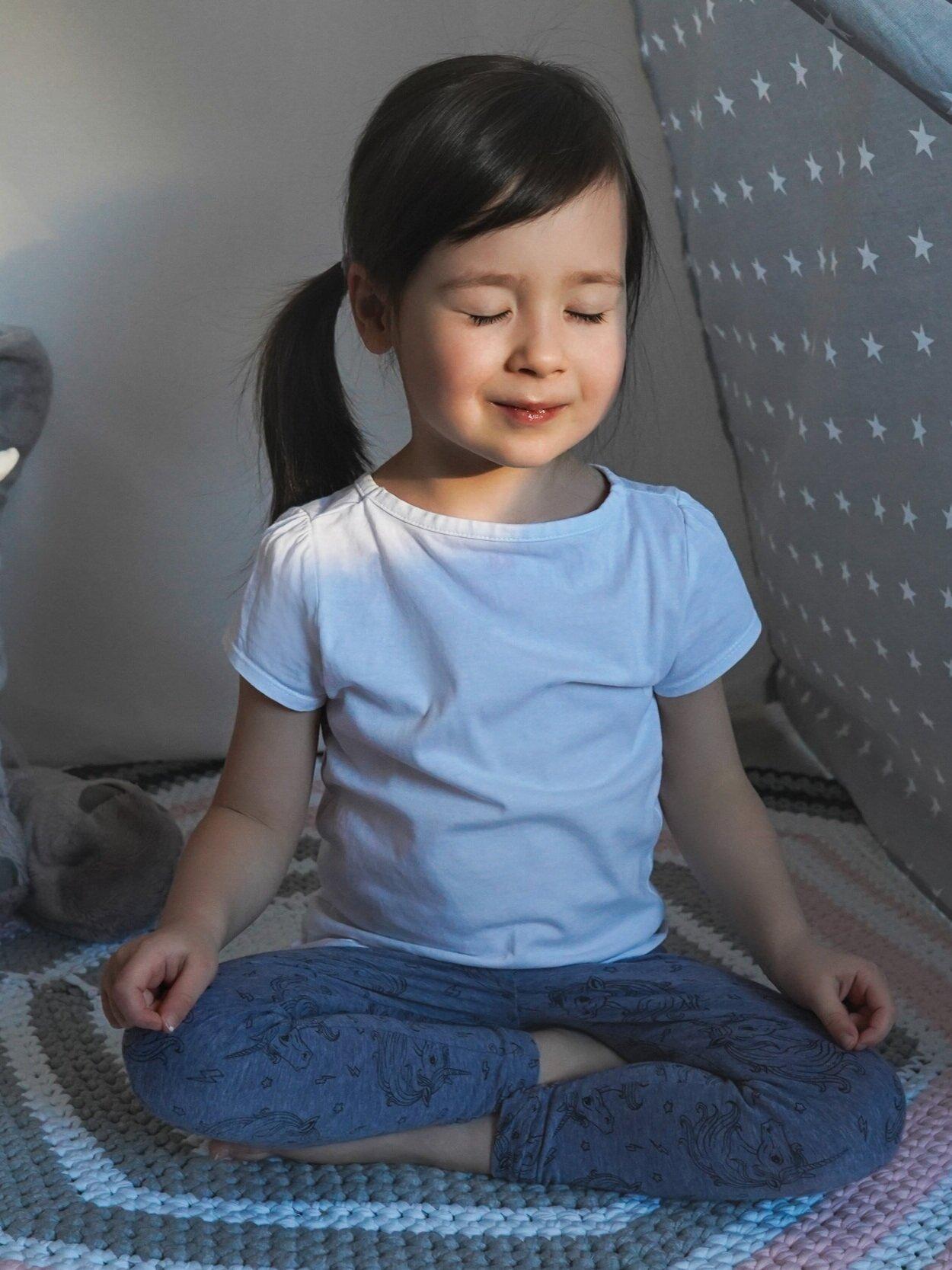 Little girl meditating in yoga pose