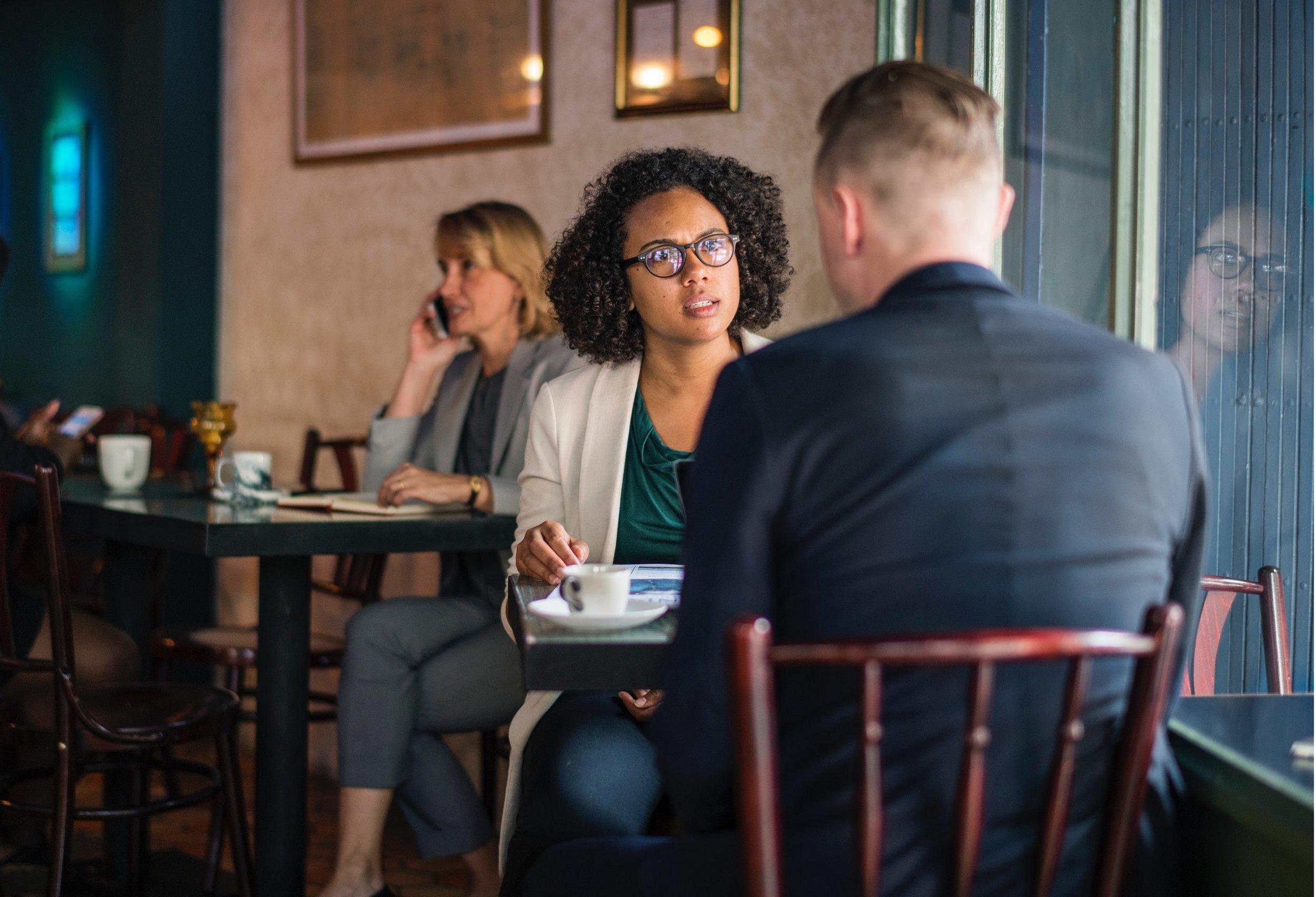 Women talking to man in cafe