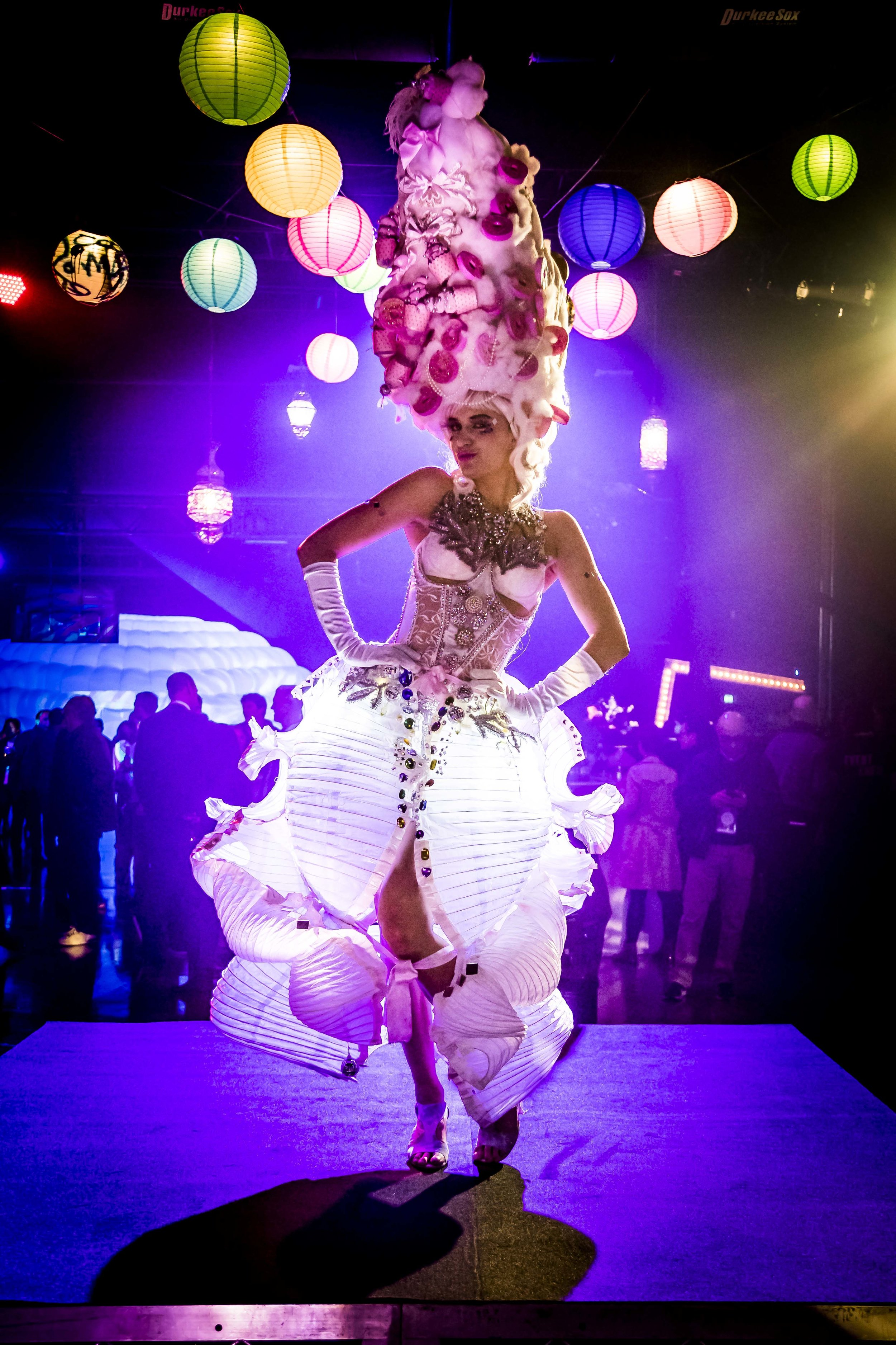 "Marie Lantern-ette - Marie Lanternette is a glowing spectacle, with her skirt made of paper lanterns lit up with camping lights! Sometimes Ms Lanternette has a collection of lanterns on long poles that she uses to light people's way and lead them from place to place. 8 foot tall and teetering in platform heels, the enormous bouffant ""wig"" strewn with cake, donuts and what appears to be fairy-floss, is the cherry on top of this spectacular luminescent look."