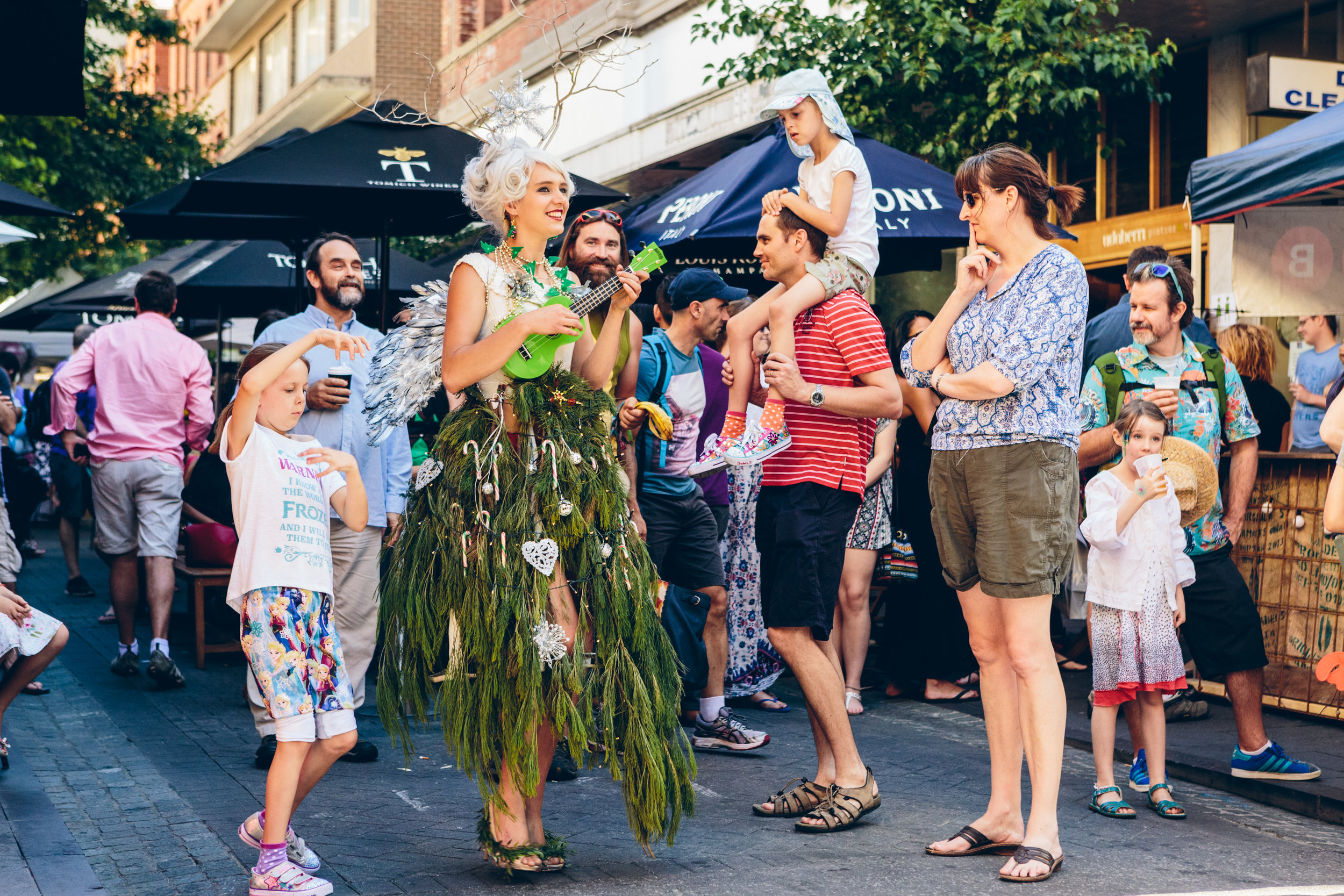 """""""Twiggy"""" the Singing Tree is at once festive and ethereal. With branches of real flora interwoven into her dress, adorned with fairy lights and candy canes, she moves slowly and gracefully.  She can be dressed for Christmas with bells on her heels and glitter in her wings, or redressed for an Australiana look, as a wattle!  She is seven-foot-tall with a striking visual presence great for any event, stationary or mobile. Her angelic voice and ukulele will charm and delight passers by who may pose for a photo, make a wish, or glean some wisdom of the forests and the stars.  She can be a glamorous host, a friendly statuesque installation, or provide light lilting tunes and cheer.  The magic of a real-life walking and singing tree is a delight indeed, and of course, battery operated Christmas tree lights so she glows in the evenings!"""