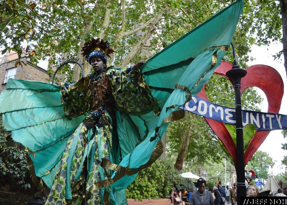 Carnival Stilt Walker promoting the community aspects of Notting Hill Carnival.  Photography by: Jeff Moh.