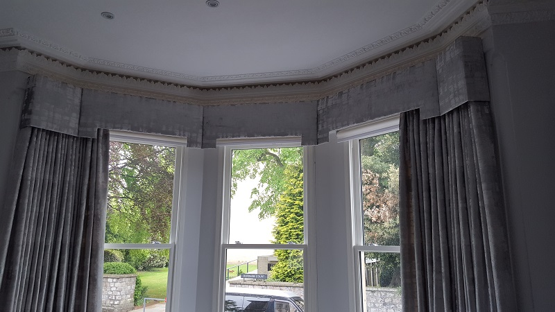 Modern silver curtains and pelmets for this fabulous bay window -