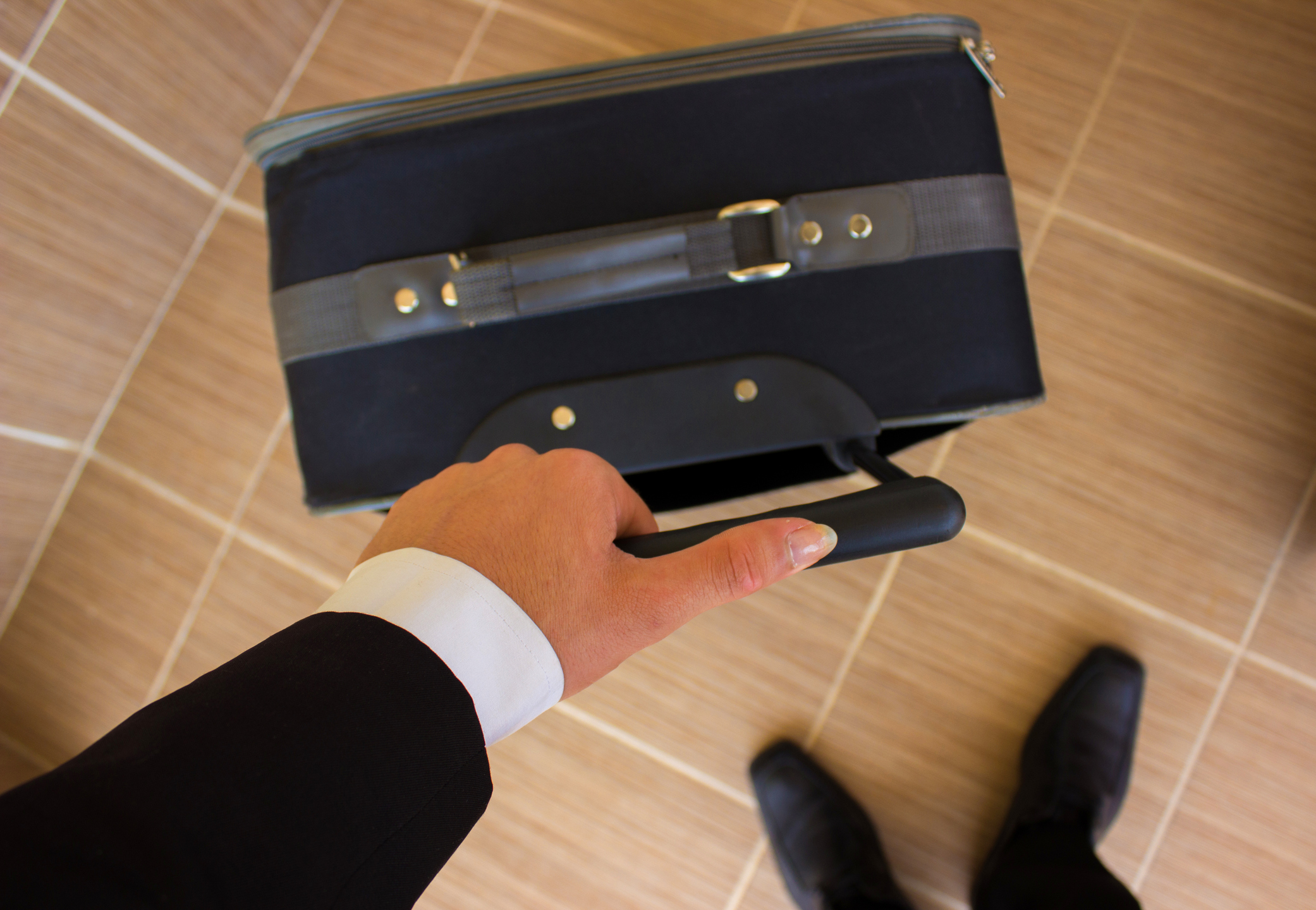 Businessman in black suit holding a suitcase's handle. High angle view,unrecognizable person. Horizontal composition. Image developed from Raw.