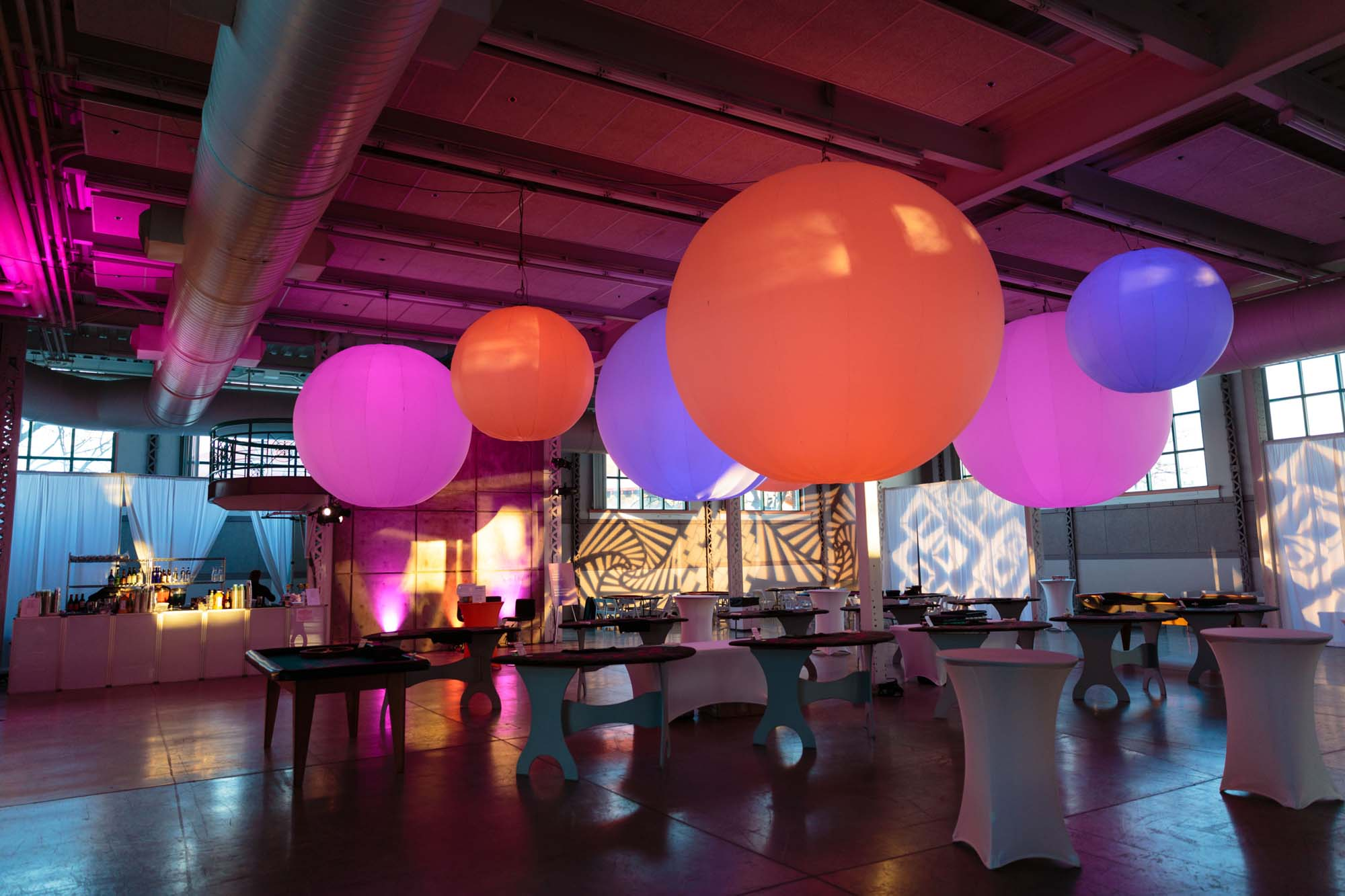 Orange, Pink and Purple Sphere H-Lights handing from Ceiling over Tables