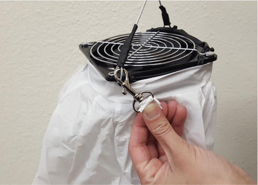 3. Next, clip the 2 metal safety hooks that are attached to the top of the cover onto the cable loops on each side of the fan,