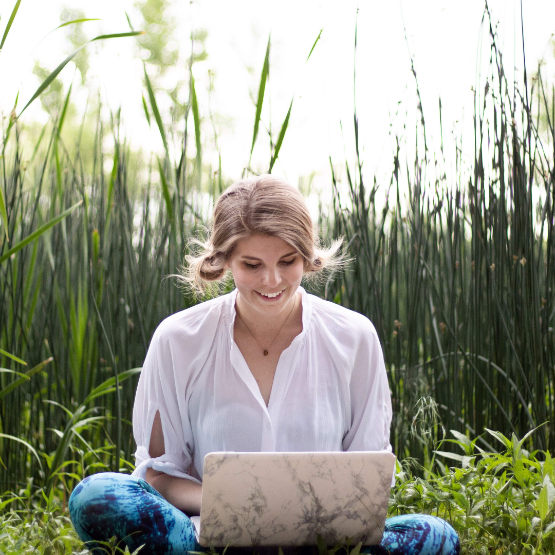 woman sitting in nature and designing on her macbook
