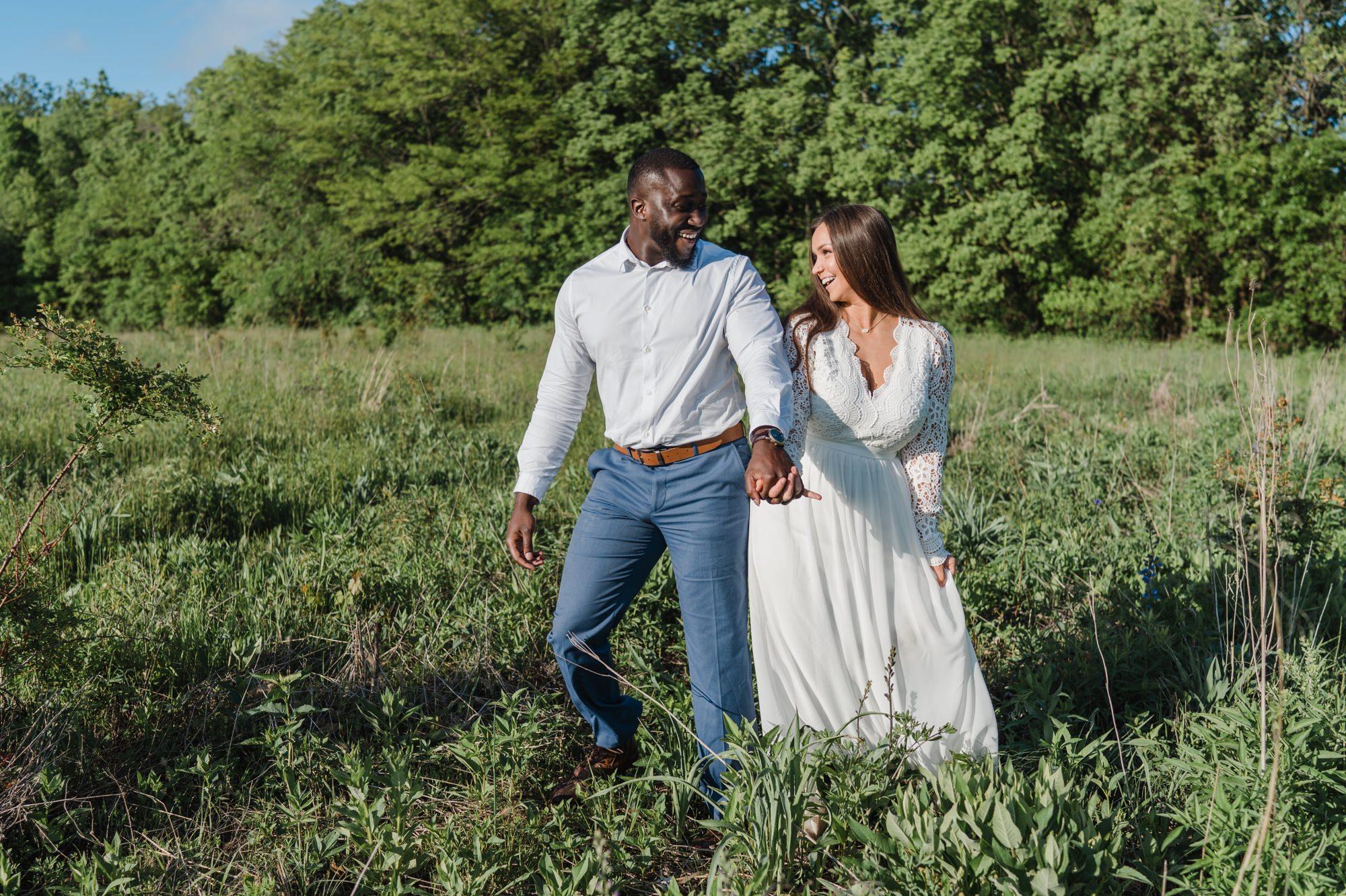couple walking together in open field at burr oak woods