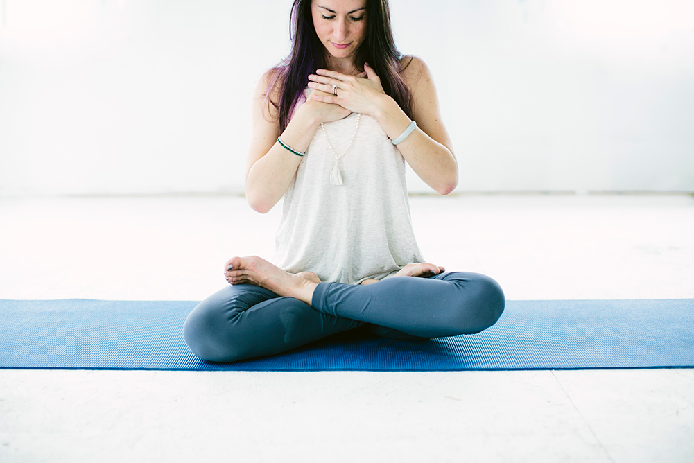 Woman on yoga mat with hands over heart