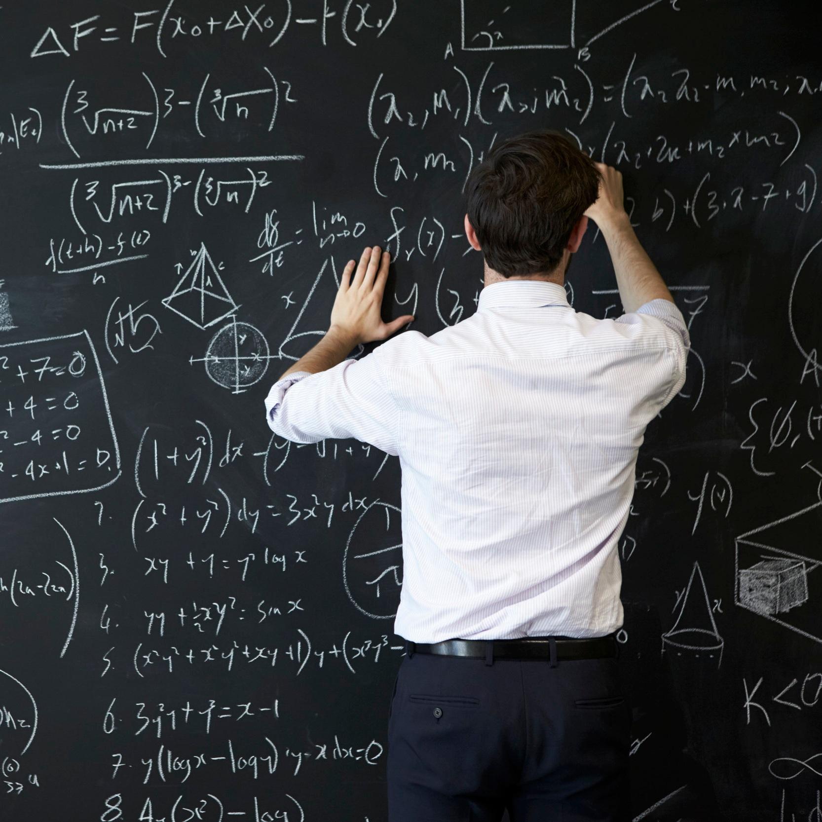 young-man-writing-on-blackboard-PU45FHT.jpg