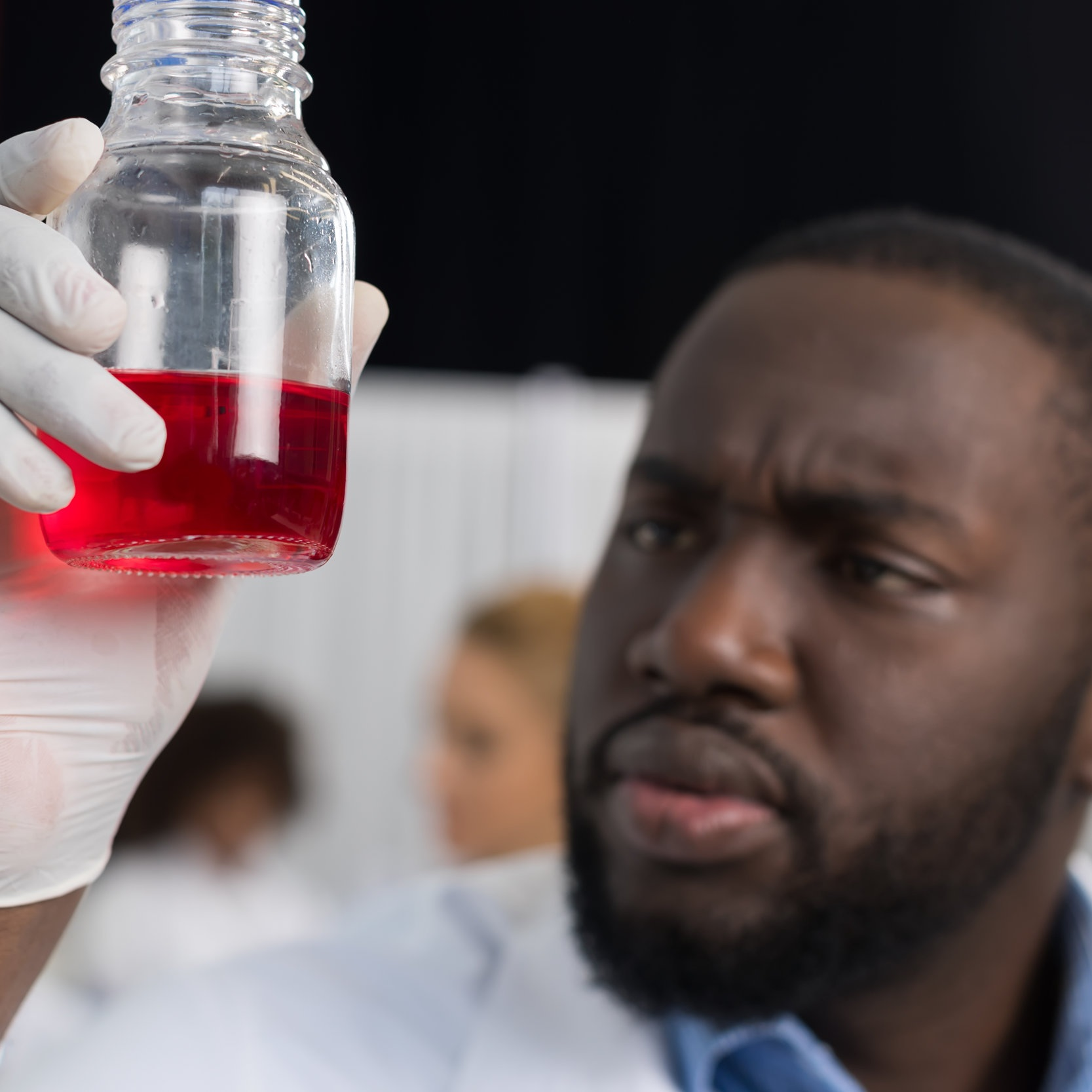 african-american-scientist-examine-flask-with-red-XP8Q9HW.jpg