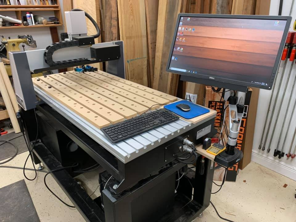 """Axiom PRO8 CNC - The CNC is a computer-controlled router essentially, though this machine sports a water-cooled spindle. Our machine is 24"""" x 48"""" and is a dream to use. The machine is controlled by Vectric VCarve Pro software.Link to Axiom Website"""