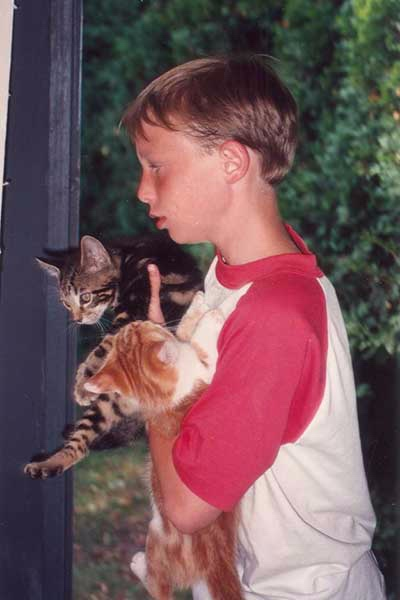 Evan as a young boy with two cats