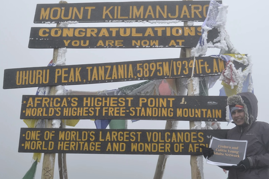 Sneha Dave at the top of Mt. Kilimanjaro. She is pictured holding a sign for the Crohn's and Colitis Young Adult Network.