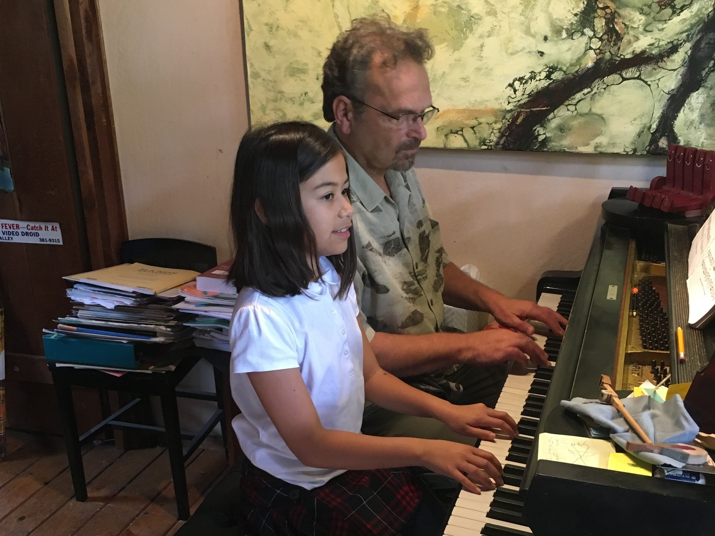 Paul Agricola, Branch President and Mill Valley piano teacher, plays a duet with his student Chloe.
