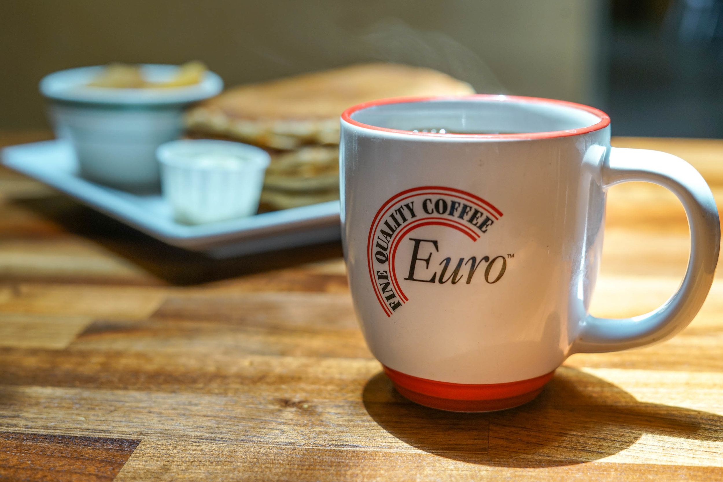 euro coffee cup with pancakes in the background