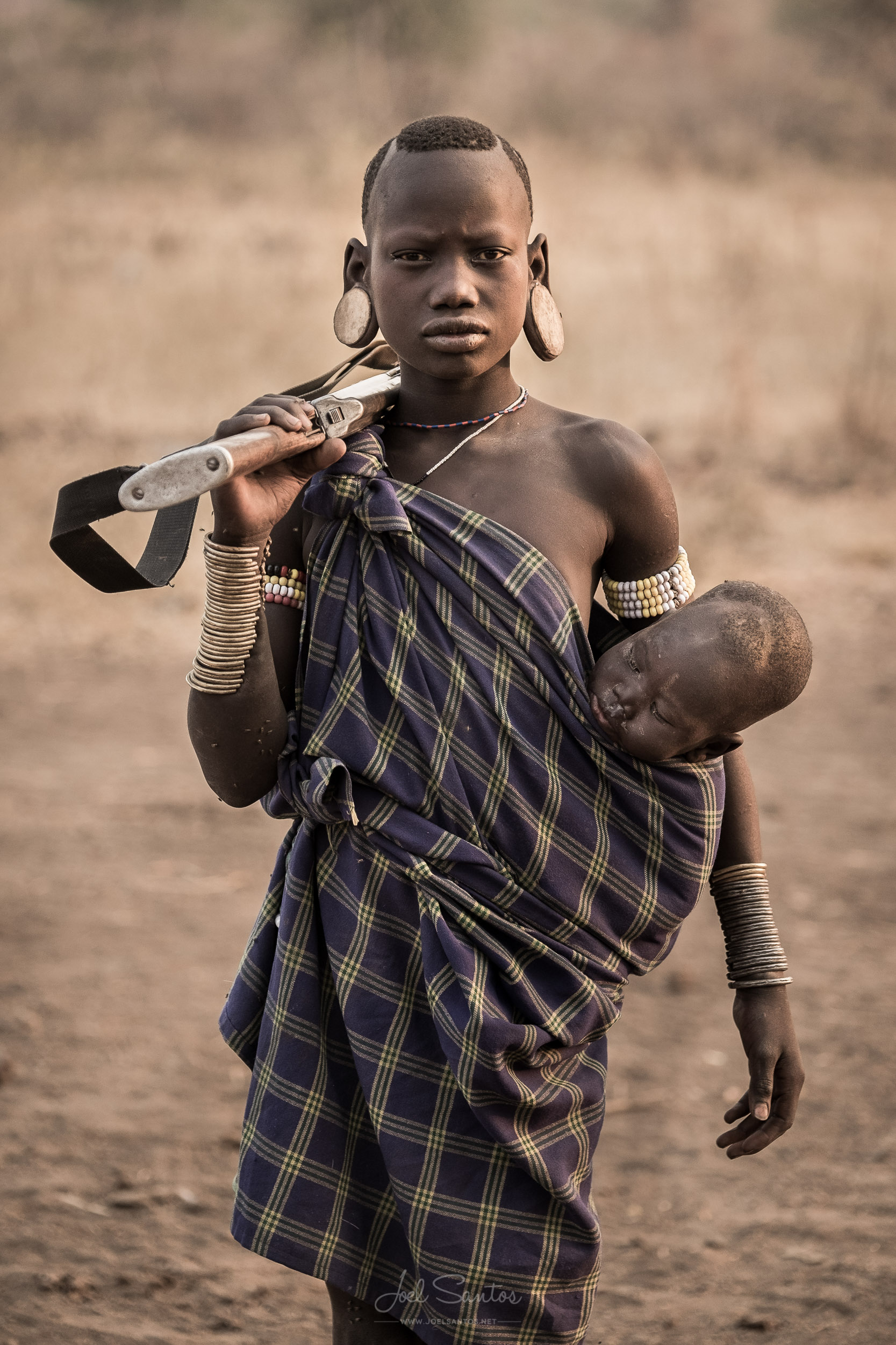 Mursi Tribe Girl holding a Baby and a Rifle, Omo Valley, Ethiopi
