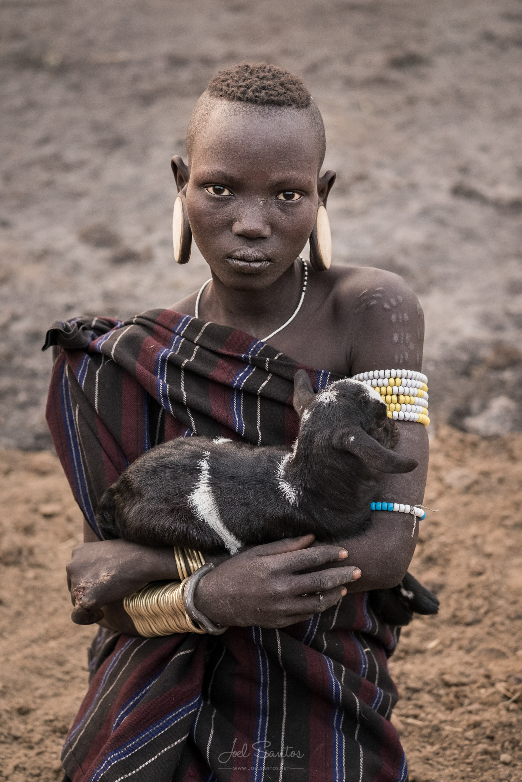 Mursi Tribe Woman holding a sheep, Omo Valley, Ethiopia