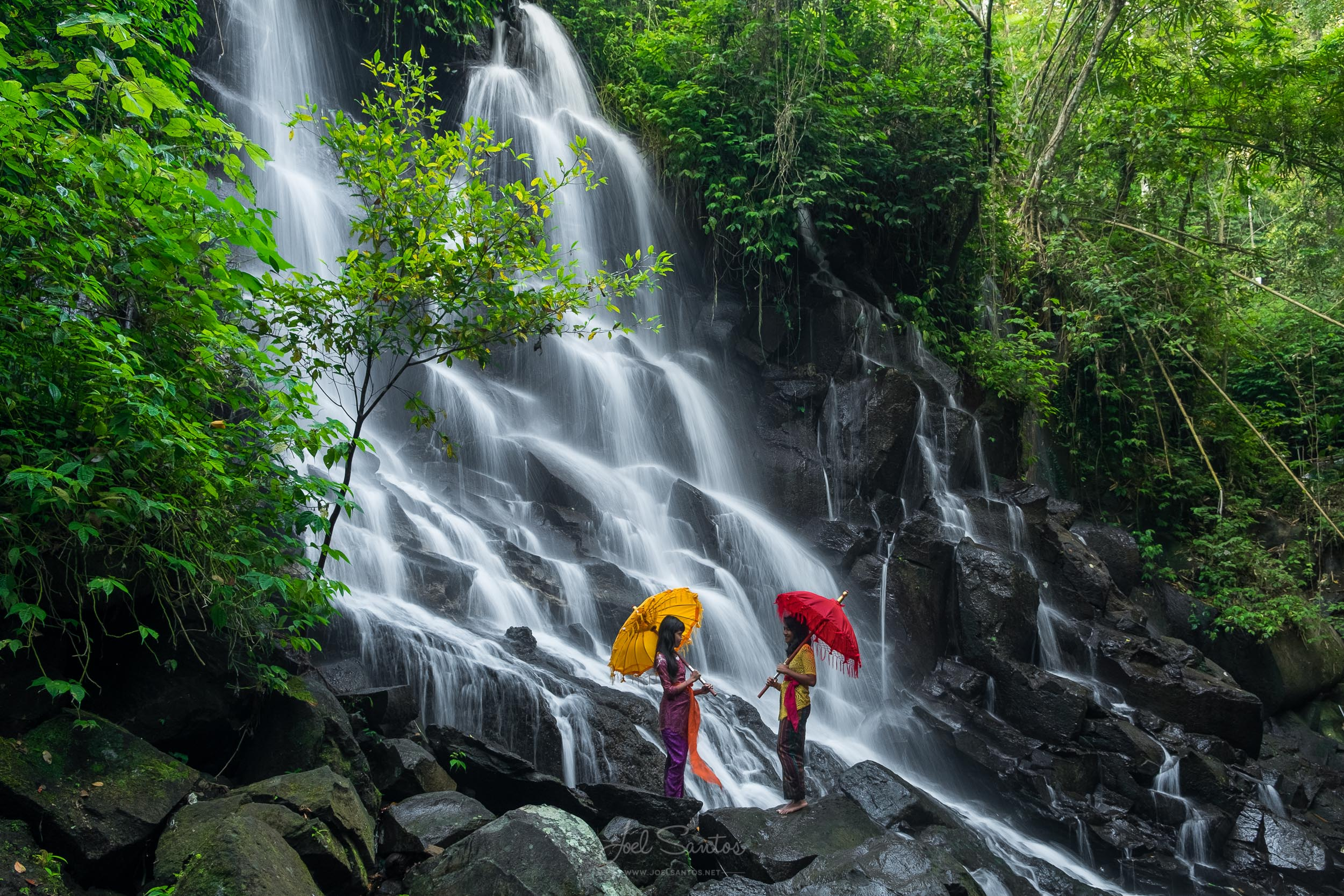Balinese Girls with traditional umbrella at Waterfall, Bali, Ind