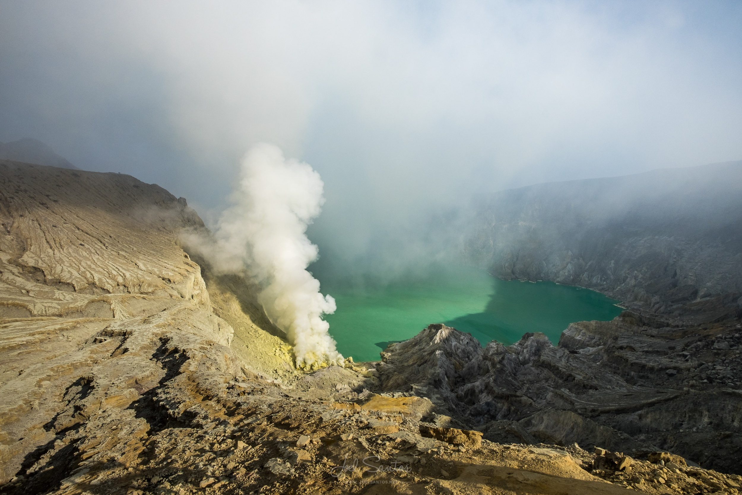 Kawah Ijen volcanic crater with turquoise blue acidal lake and s