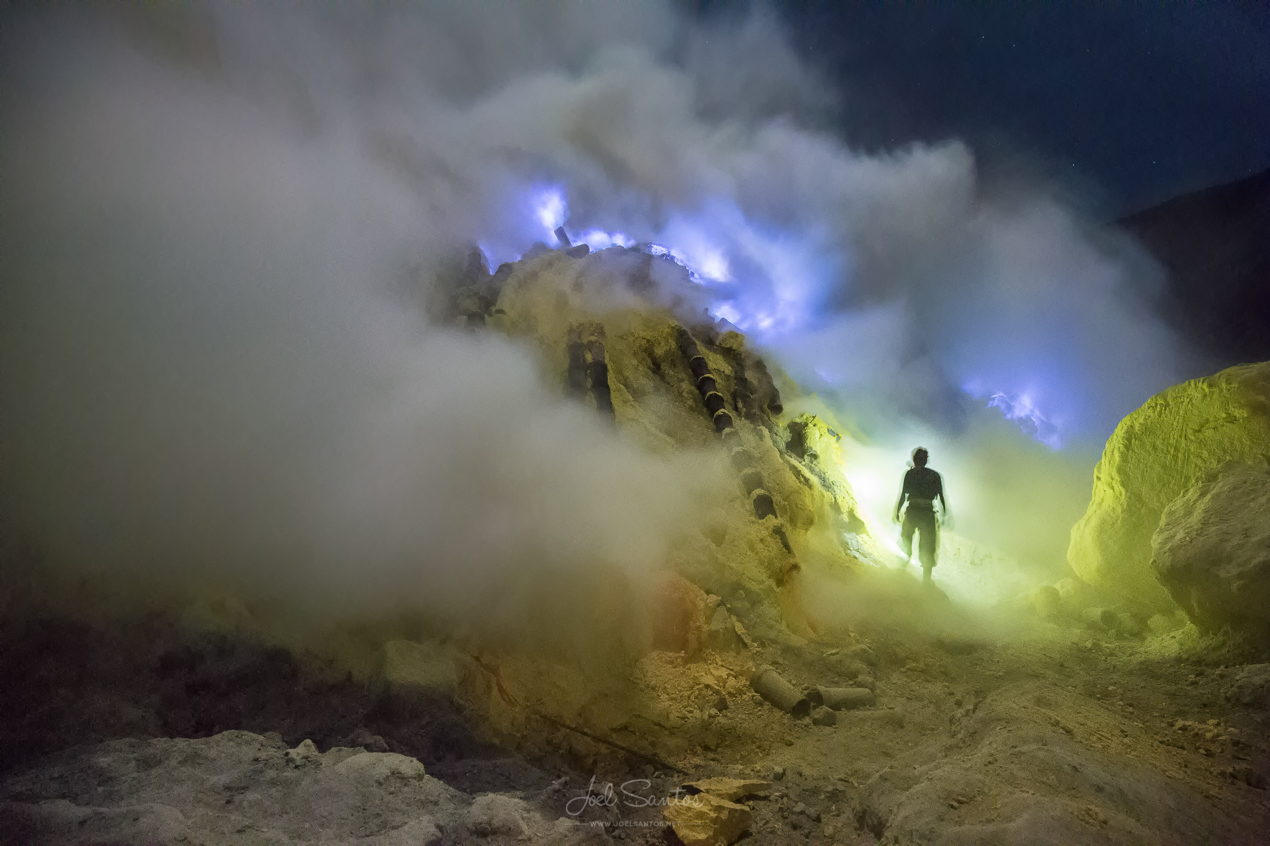 Miner working surrounded by sulphur fumes and gases, Kawah Ijen