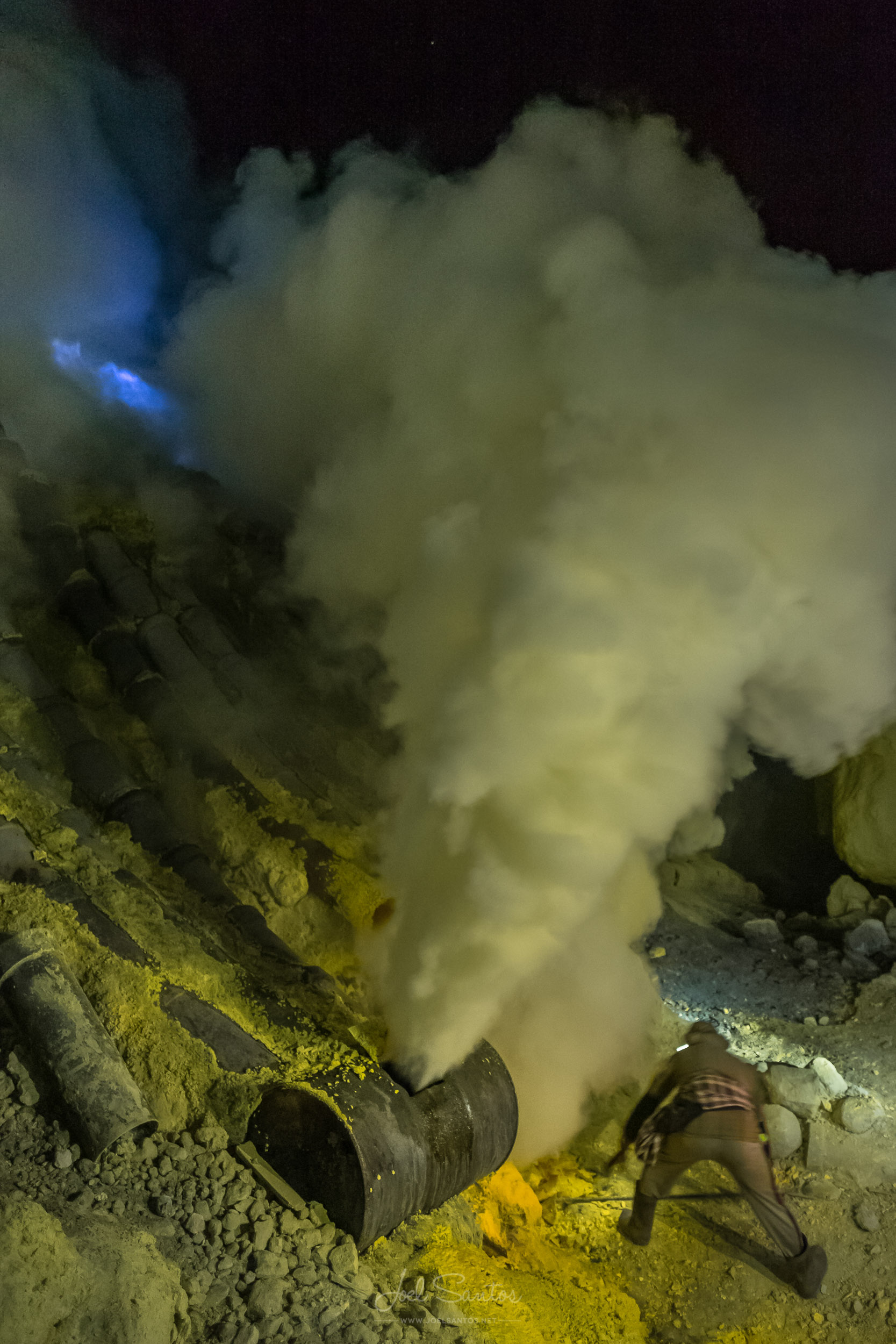 Miner working and breaking sulphur blocks, surrounded by fumes a
