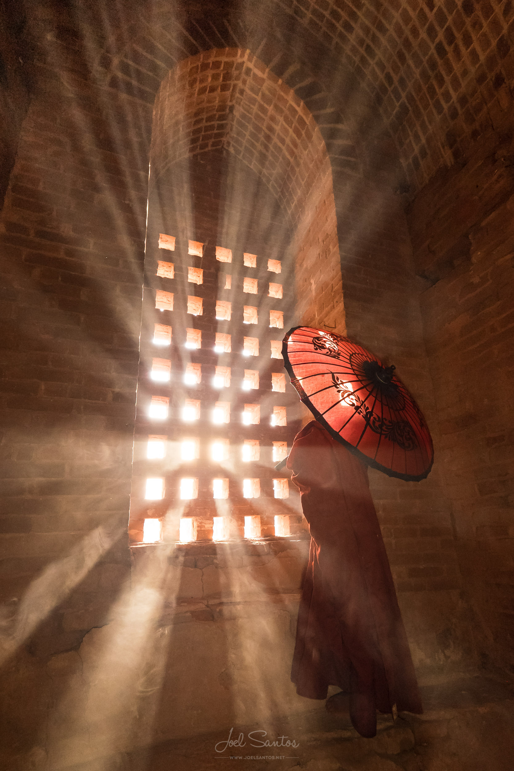 Novice buddhist monk with umbrella lit by sun rays, Bagan, Burma