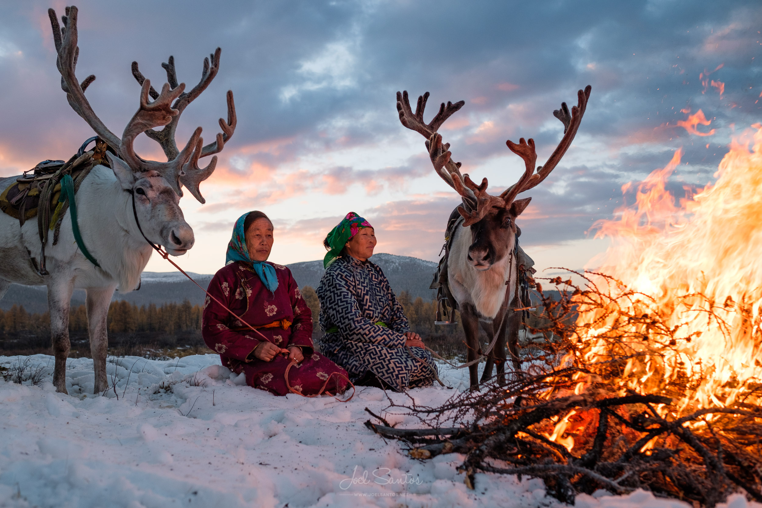 Purev and Buyantogtokh enjoy the warmth of the fire in the cold Mongolian weather