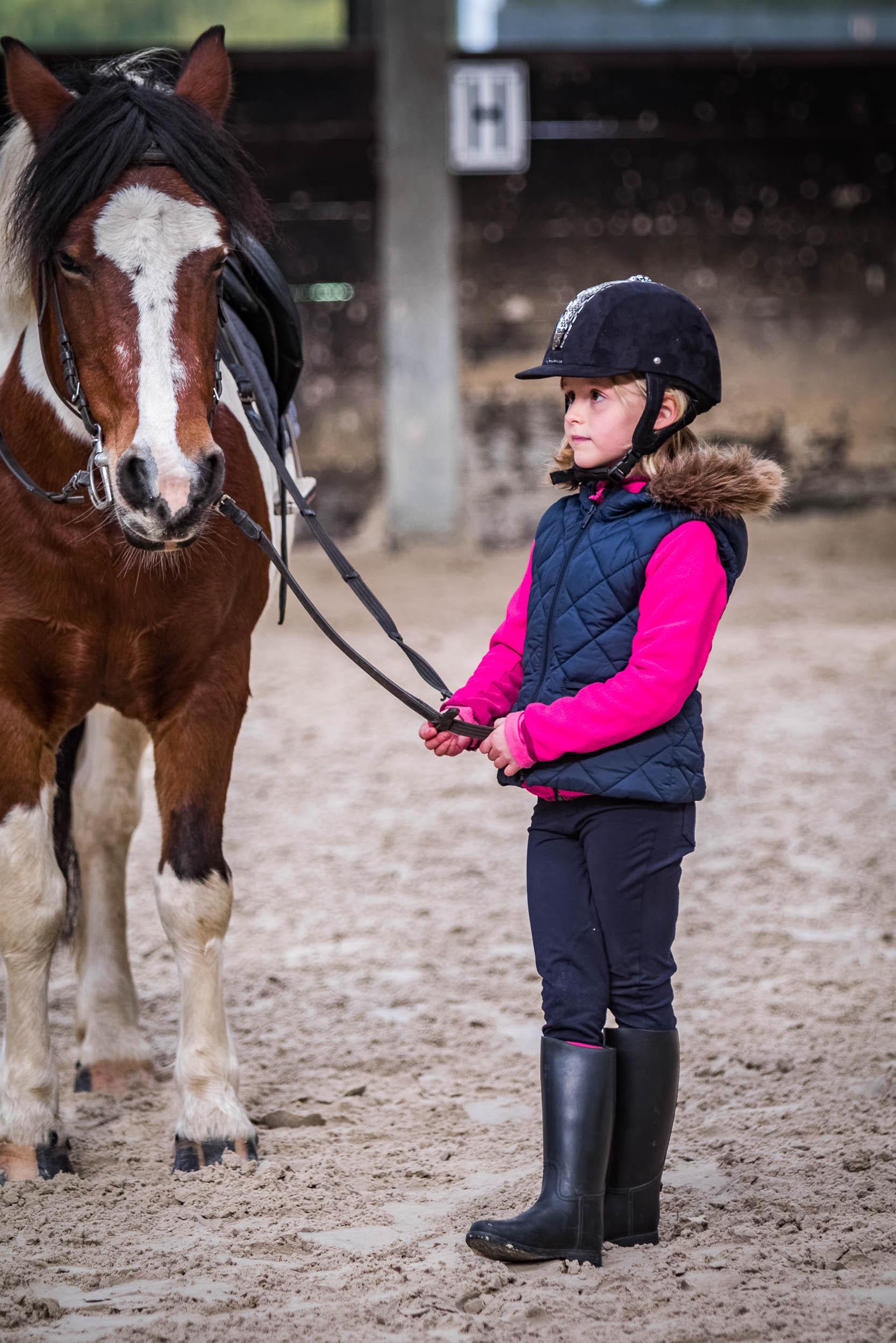 Petite fille faisant de l'équitation. Photo prise par un photog