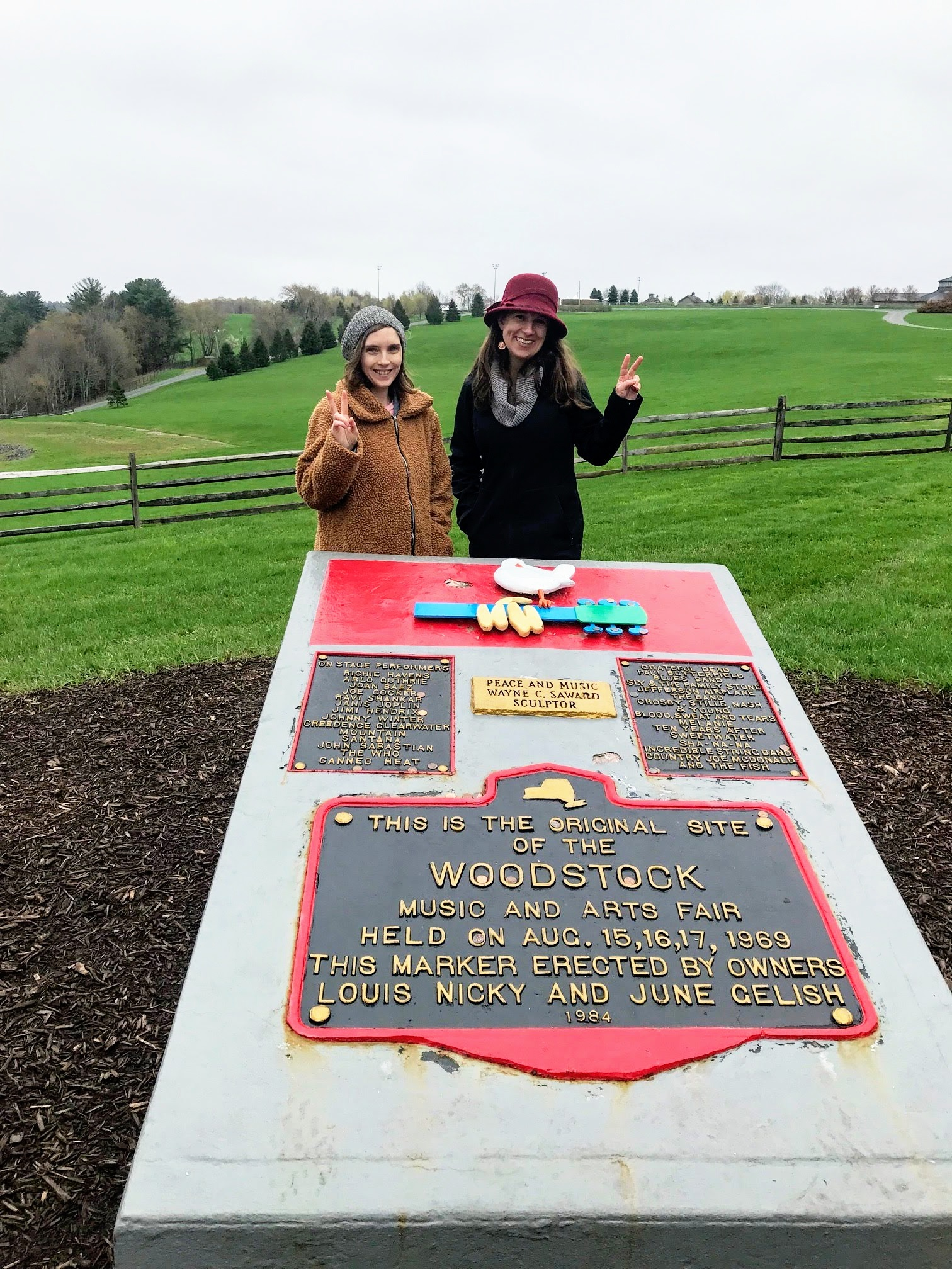 The League's Katy Peace and Erin Tobin pose with the Woodstock site marker