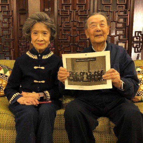 Gloria and Tao Tai Hsia at their home in Washington. Tao Tai holds a photo of Bachelor Harry Rudin in 1921.