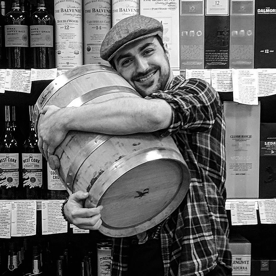 George hugging a barrel of Journeyman Distillery's Silver Cross that he selected for Parkway Wine & Liquor in front of the 'Great Wall of Whiskey'