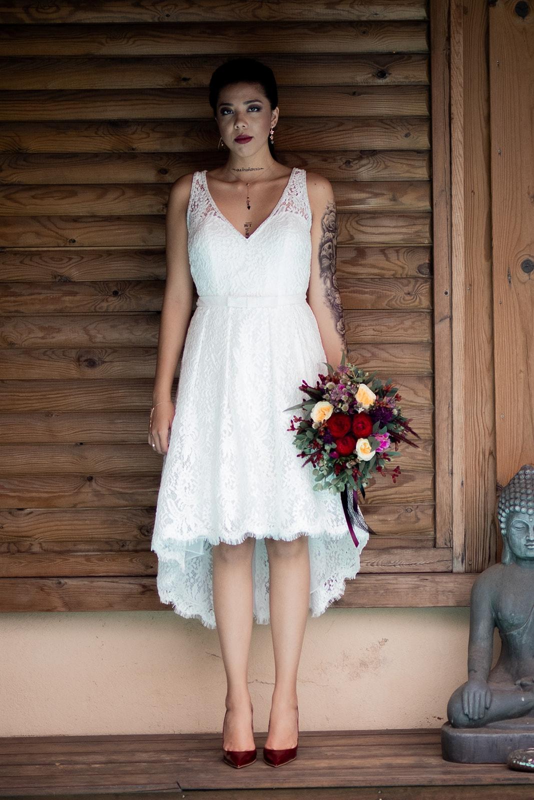 La robe - Optez pour une robe courte, plus moderne est dans l'ère du temps. Nous, on a choisi cette robe asymétrique sans manche de la boutique Rosa Clara. Alliez confort, élégance et glamour. Une robe qu'on peut porter de la cérémonie à la réception. De plus, si comme Shayna vous avez des tatouages, cela mettra en valeur votre style. Et pour monsieur adoptez un style moins traditionnel en accord avec votre thème Rock & roll.