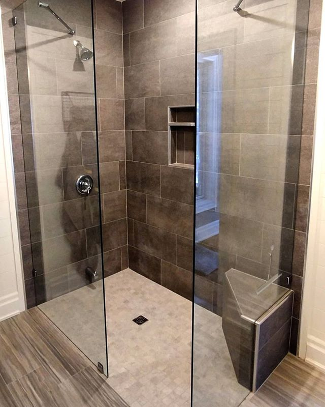 Custom walk-in curbless shower with floating corner bench. Full Schluter Systems waterproofing. Italian porcelain with Rondec brushed chrome accents. Has a nice open and modern feel.  Let bulky curbs and glass doors be a thing of the past.