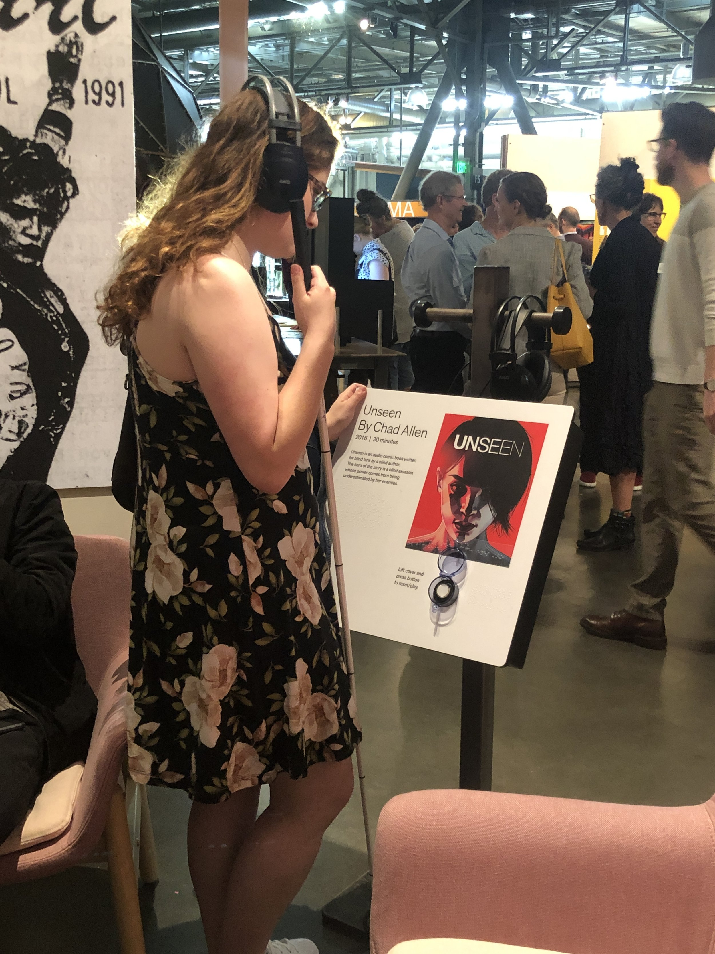 Lauren, a blind attendee listening to Unseen at the exhibit opening night