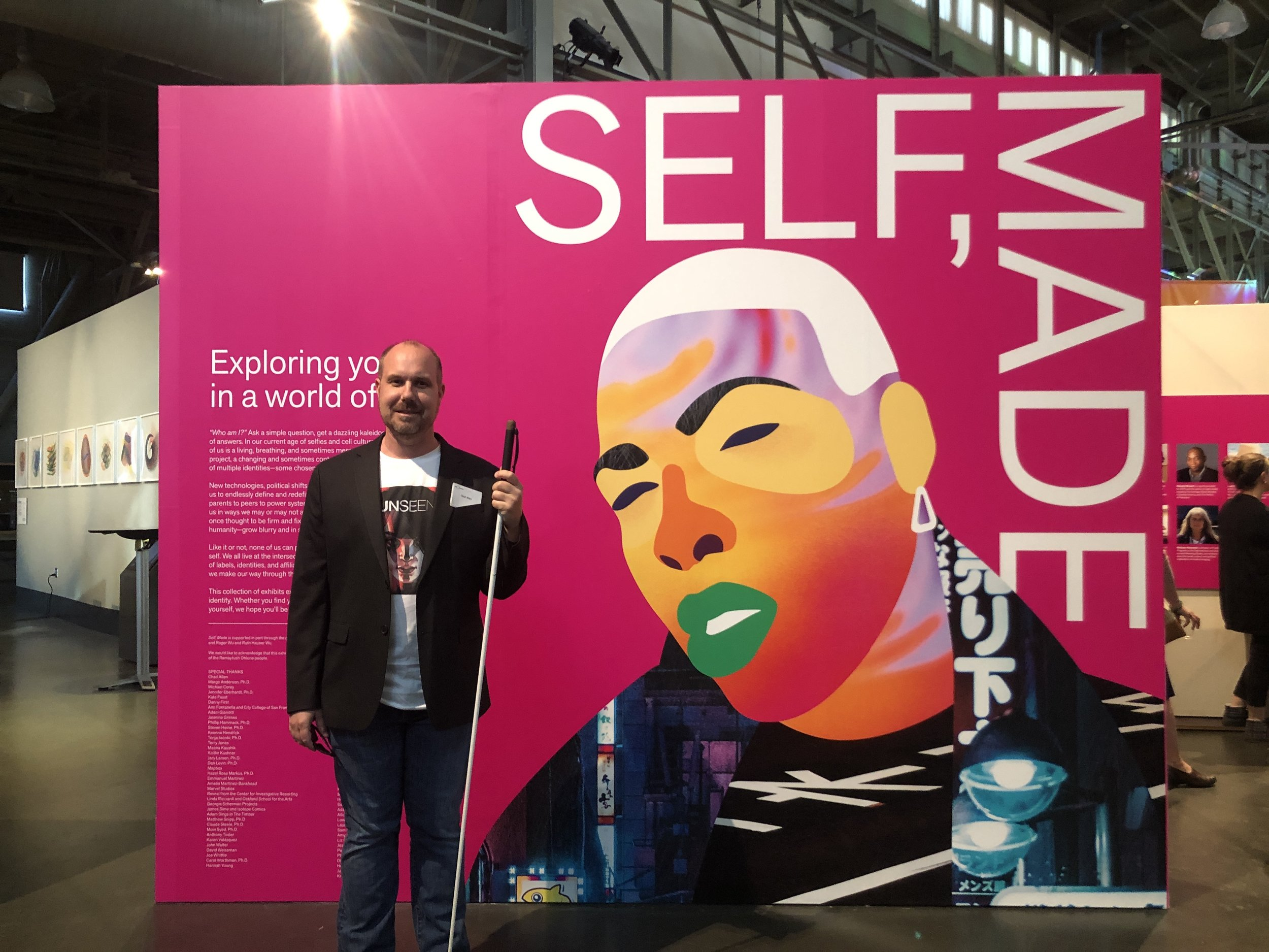 Chad Allen, author in front of the Self, Made exhibit signage.