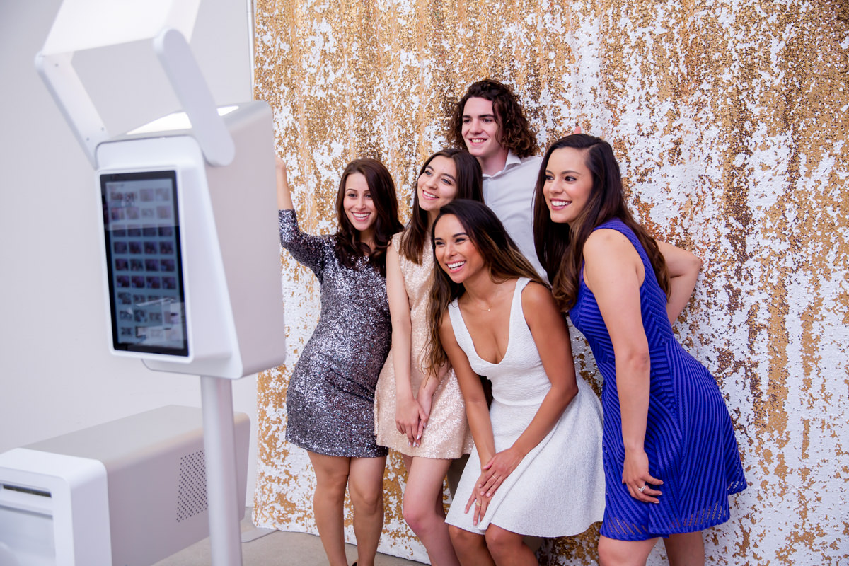 women in front of a sequin backdrop taking a photobooth picture