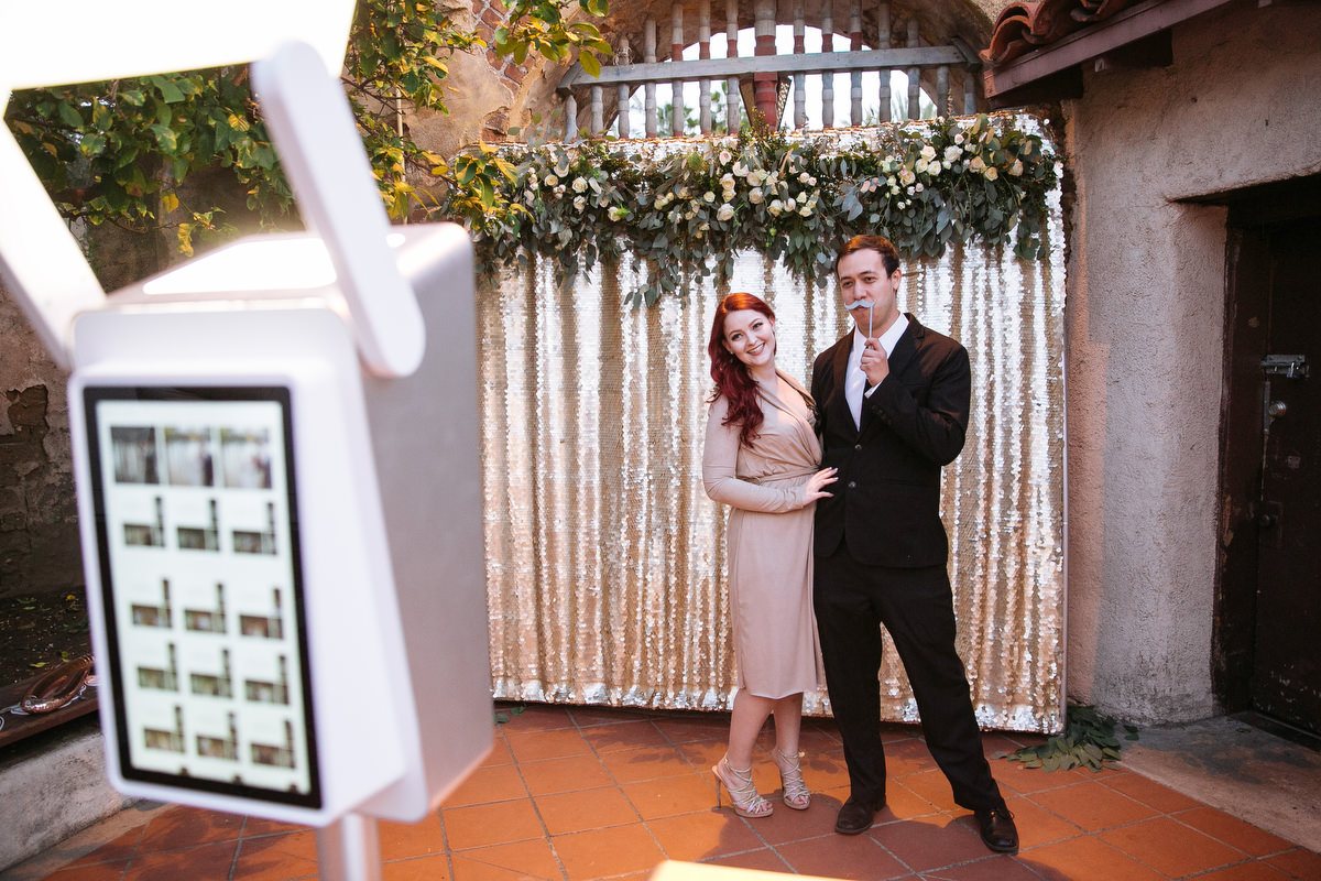 couple enjoying the photo booth at a wedding in front of a Gold backdrop with floral accent