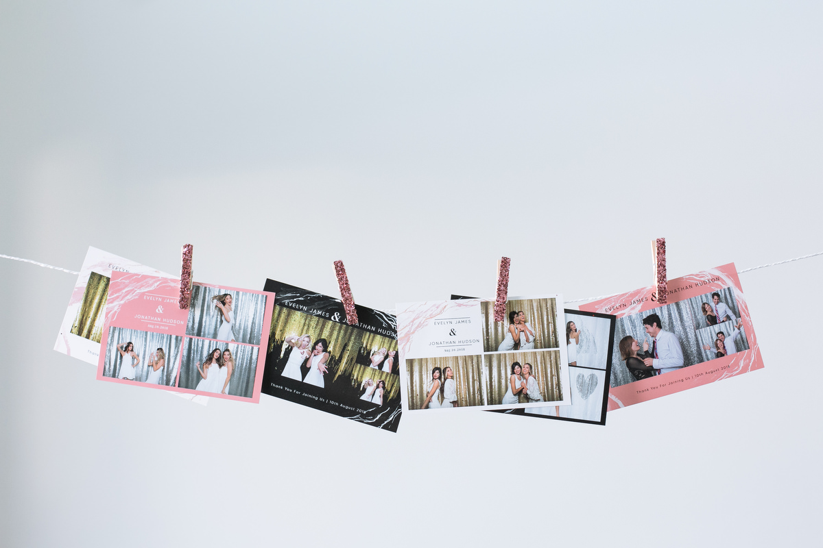 Wedding photo booth prints hanging on a line