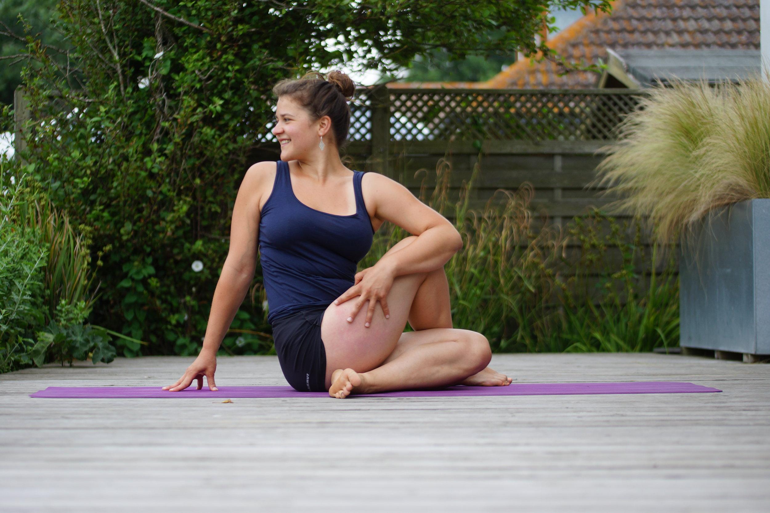 Ardha Matsyendrasana - Halbe Drehsitz, das linke Bein anstellen, den linken Fuß außen an das rechte Knie setzen, nach Möglichkeit die rechte Ferse außen an die linke Hüfte bewegen, mit der rechten Ellbeuge um das linke Knie greifen, über die linke Schulter nach hinten schauen. Mit dem Einatmen leicht den Rücken strecken, mit dem Ausatmen die Drehung vertiefen. Das Gewicht gleichmäßig auf dem Hintern verteilen, das rechte Bein entspannen
