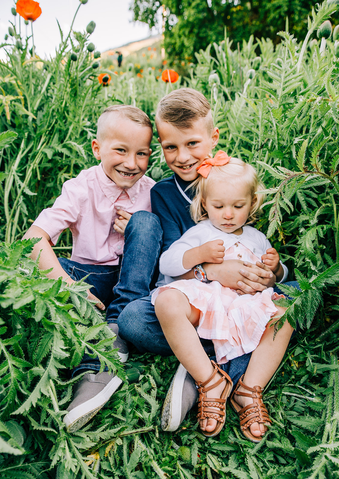 Adorable smiling kids during family pictures in Cache Valley, Utah by professional family photographer Bella Alder Photography. Looking for someone to capture your family pictures this year? Check out Bella Alder! #bellaalderphoto #familyphotog #familyphotography #familypictures #familyphotos #outfitinspo #familyoutfits #poppyfields #northernutahfamilyphotographer #utahfamilyphotographer #cachevalleyfamilyphotographer