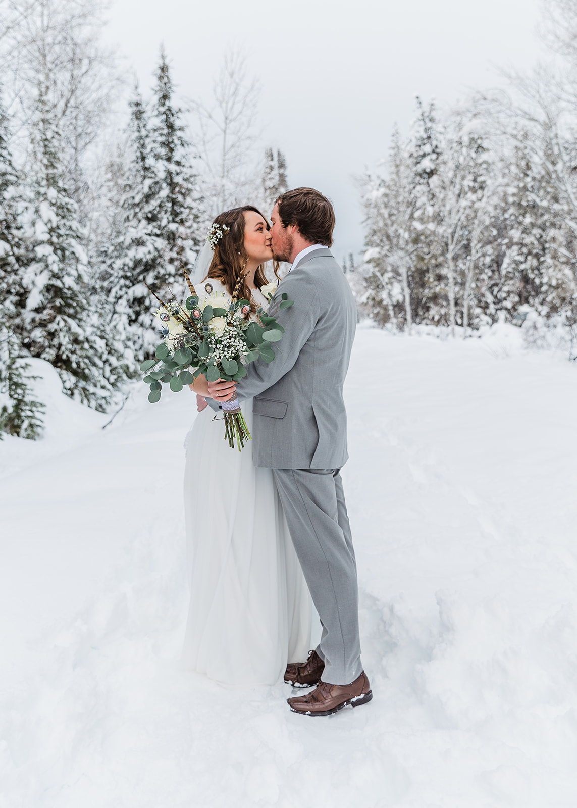 kissing couple pose in the woods snowy day photography womens wedding  hairstyle lose curls long and romantic white flowers in her hair grey mens wedding suit romantic wedding couples portrait formal wedding pictures tony's grove in cache valley #winterwedding #formals #tony'sgrove #cachevalley #snowcoveredtrees #bellaalderphotography #professionalphotographer #winterwonderland #couplegoals #weddingattire
