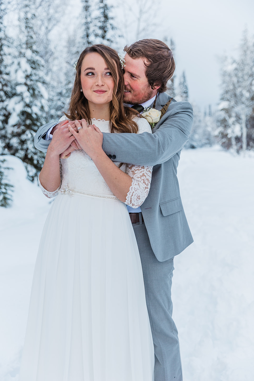 hugging the bride cheeky bridal picture love is in the air simple elegant wedding hair ideas inspiration for winter wedding pictures rosy cheeks in tony's grove cache valley loving couple couple goals winter wonderland love in the snow #winterwedding #formals #tony'sgrove #cachevalley #snowcoveredtrees #bellaalderphotography #professionalphotographer #winterwonderland #couplegoals #weddingattire