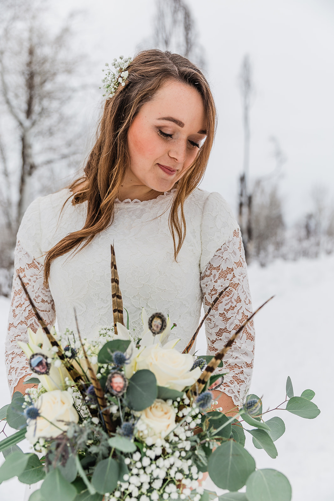 winter bridals white and green bouquet feathers in bouquets inspiration pheasant fethers beautiful modest wedding dress lace sleeves white flowers in her hair romantic bridals just the bride winter scenery professional wedding photography #winterwedding #formals #tony'sgrove #cachevalley #snowcoveredtrees #bellaalderphotography #professionalphotographer #winterwonderland #couplegoals #weddingattire