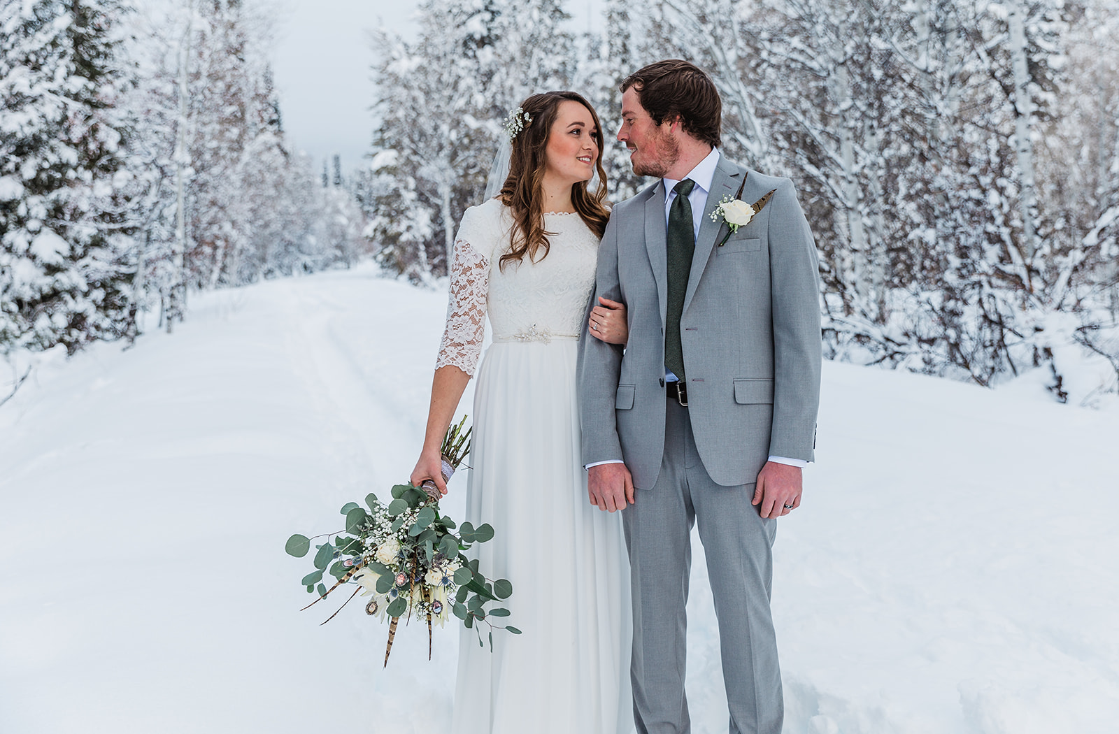 loving rustic country couple unique pheasant touches beautiful wedding dress belt rosy cheeked couple christmas season winter wedding holding grooms arm pose inspiration standing in the snow couple staring into each others eyes love is in the air #winterwedding #formals #tony'sgrove #cachevalley #snowcoveredtrees #bellaalderphotography #professionalphotographer #winterwonderland #couplegoals #weddingattire