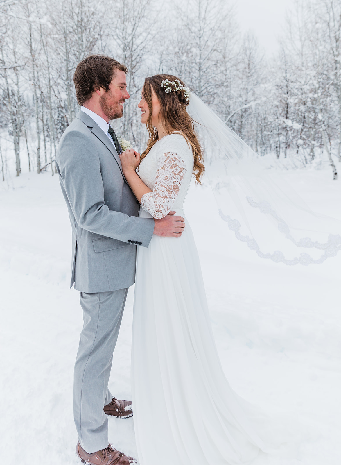 happy couple lace wedding veil flowing beautiful wedding attire elegant wedding hairstyle inspiration beautiful lace accents covered in white couple pose inspiration graceful bride professional utah photographer marriage goals man and wife #winterwedding #formals #tony'sgrove #cachevalley #snowcoveredtrees #bellaalderphotography #professionalphotographer #winterwonderland #couplegoals #weddingattire